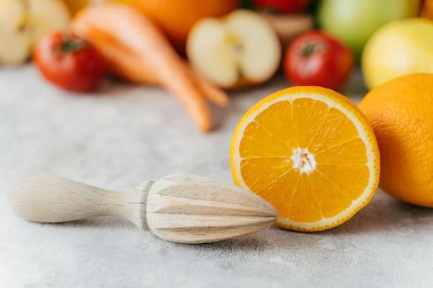 Presse-agrumes en tranches d'orange et en bois sur fond flou de fruits et de légumes.