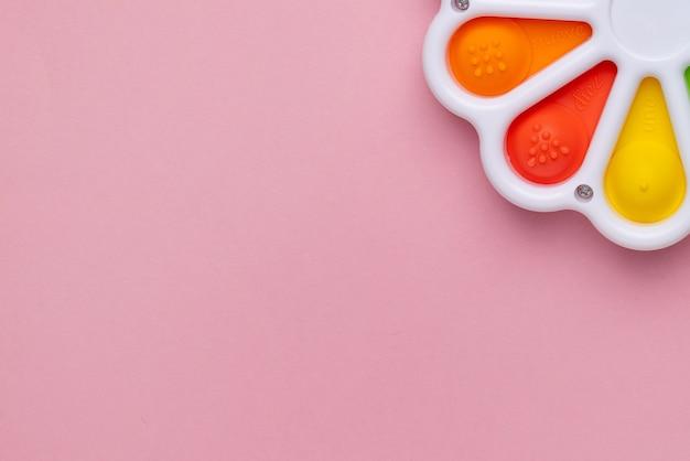 Presse avec un doigt jouet antistress pop it sur fond rose jouet poppit en silicone coloré bulle f...