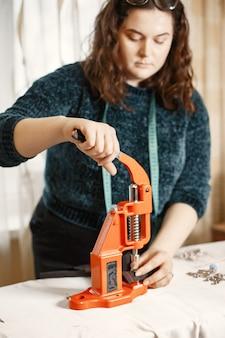 Presse orange pour les vêtements. boutons sur tissu. femme avec des outils de couture