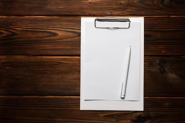 Presse-papiers blanc avec feuille de papier vierge et stylo