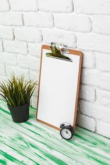 Presse-papiers en bois bureau debout contre le mur de briques blanches, espace copie