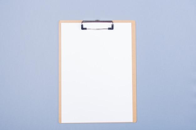 De presse-papiers en bois avec du papier vierge isolé sur fond gris clair. espace libre. copiez l'espace.