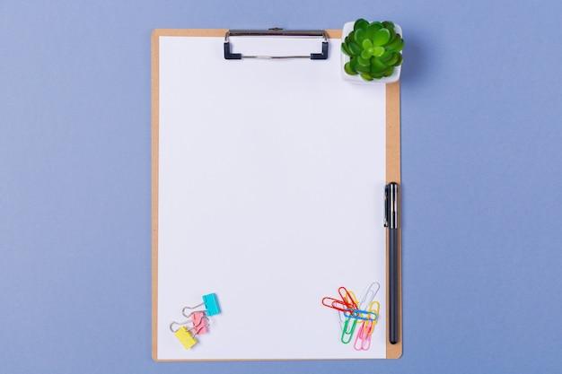De presse-papiers en bois avec papier vierge, stylo, papeterie sur fond gris clair. espace libre. copiez l'espace. vue de dessus.