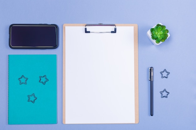De presse-papiers en bois avec papier vierge, stylo, papeterie, téléphone intelligent sur fond gris clair. espace libre. copiez l'espace. vue de dessus.