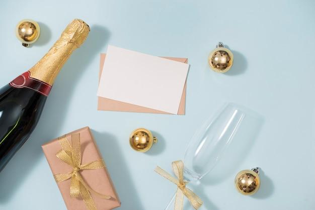 Presse-papiers et bouteilles de champagne avec décorations dorées. mise à plat, concept de vacances à la mode vue de dessus.
