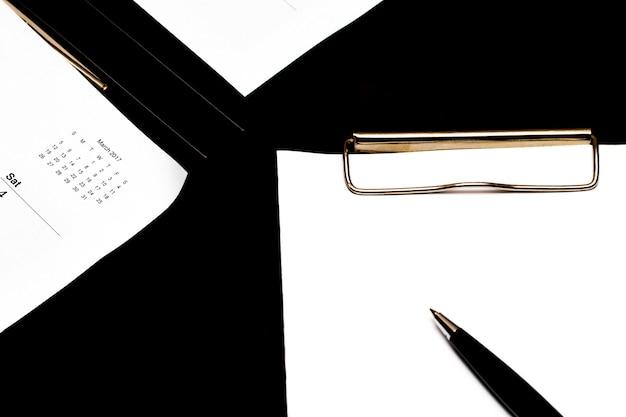 Presse-papiers et calendrier sur une surface noire