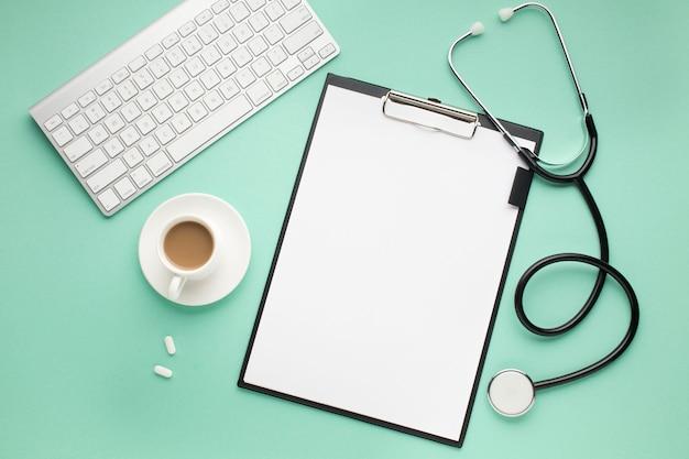 Presse-papiers; clavier sans fil; tasse de café et stéthoscope sur le bureau vert
