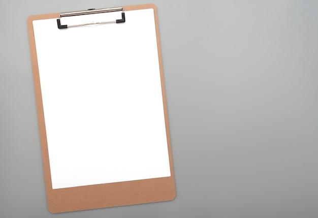 Presse-papiers avec du papier blanc blanc propre pour le texte, des idées sur fond gris, vue de dessus