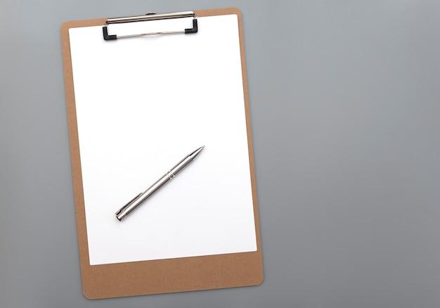 Presse-papiers avec du papier blanc blanc propre et un stylo en fer argenté sur fond gris, vue de dessus