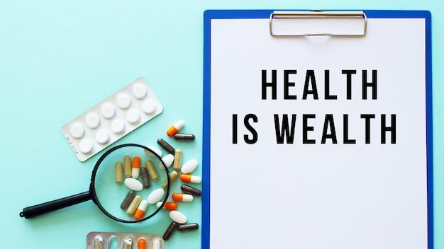 Un presse-papiers avec du papier se trouve sur une table près de médicaments et d'une seringue. inscription la santé c'est la richesse