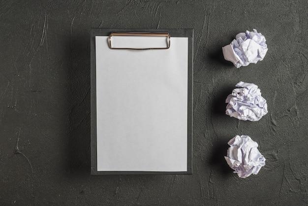 Presse-papiers avec du papier vierge à côté des papiers froissés dans une rangée