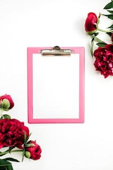 Presse-papiers avec espace copie vierge dans le cadre de fleurs de pivoine rose sur une surface blanche