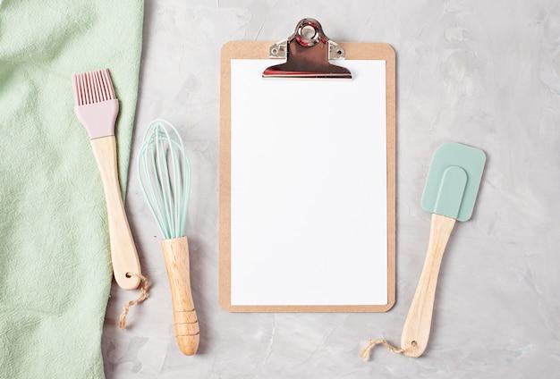 Presse-papiers avec espace vide et ustensiles de cuisine vue de dessus
