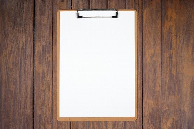 Presse-papiers avec feuille blanche sur fond de bois marron