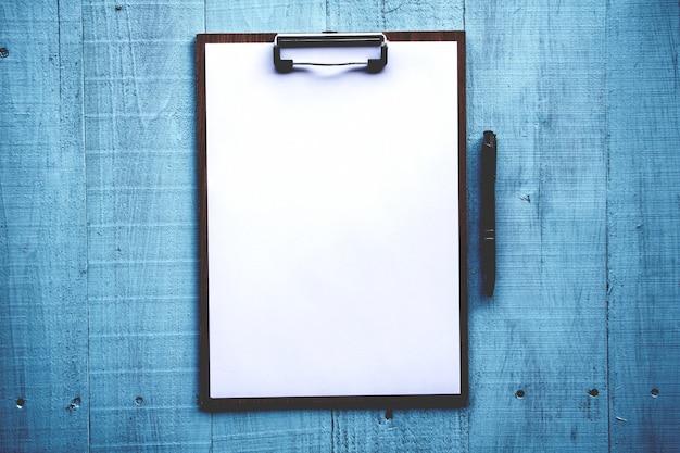 Presse-papiers avec une feuille blanche sur fond de bois
