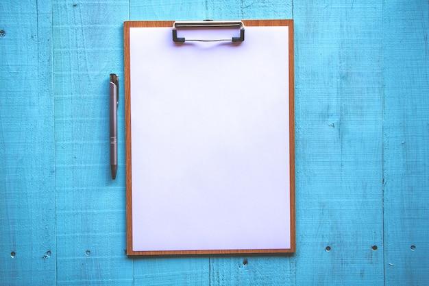 Presse-papiers avec une feuille blanche sur fond de bois.