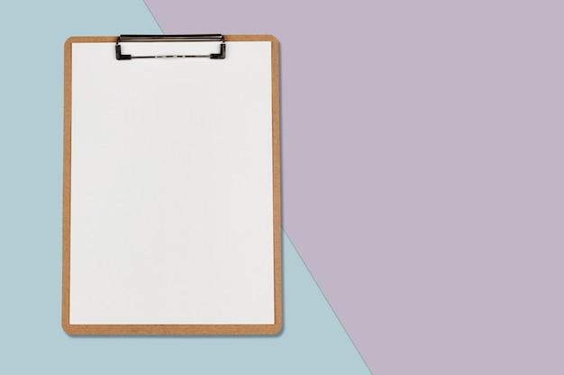 Presse-papiers avec une feuille blanche sur fond de couleur pastel, concept minimal