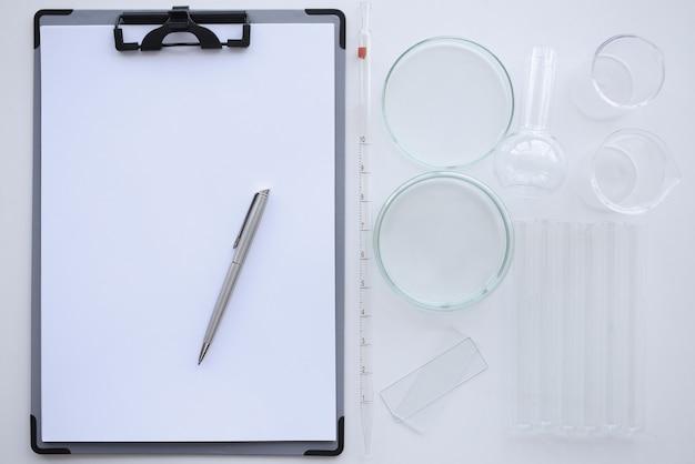 Presse-papiers avec feuille blanche et stylo se trouve sur la table à côté des boîtes de pétri