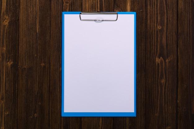 Presse-papiers avec une feuille de papier blanc vierge sur bois