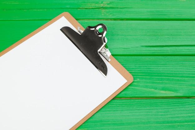 Presse-papiers avec une feuille de papier vierge blanche sur l'espace de copie en bois vert