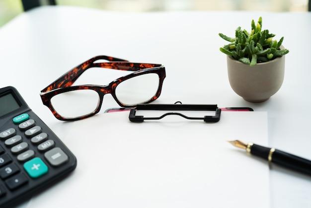 Presse-papiers avec une feuille de papier vierge, stylo, lunettes et calculatrice sur blanc