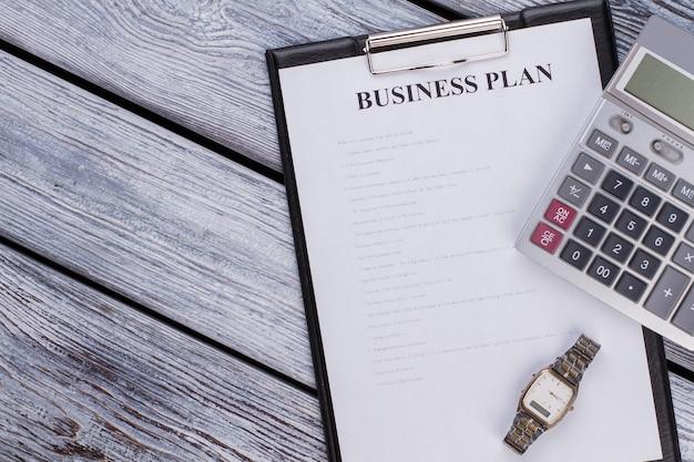Presse-papiers avec feuille de plan d'affaires et calculatrice sur table en bois blanc. vue de dessus à plat.