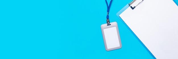 Presse-papiers avec feuille vierge et badge nominatif en plastique avec cordon bleu sur surface bleu clair