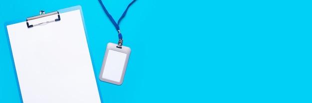 Presse-papiers avec une feuille vierge et un badge nominatif en plastique avec de la dentelle bleue sur une surface bleu clair
