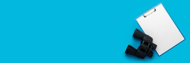 Presse-papiers avec une feuille vierge et des jumelles sur fond bleu. concept d'embauche, aide recherchée. bannière. mise à plat, vue de dessus.