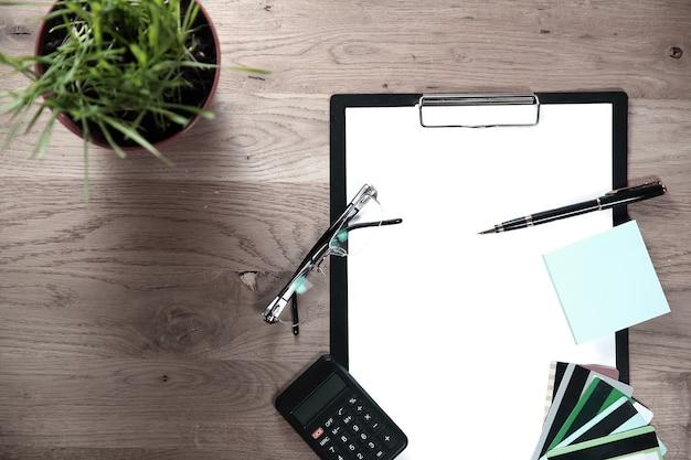 Presse-papiers avec feuille vierge, stylo, lunettes et calculatrice sur fond en bois.