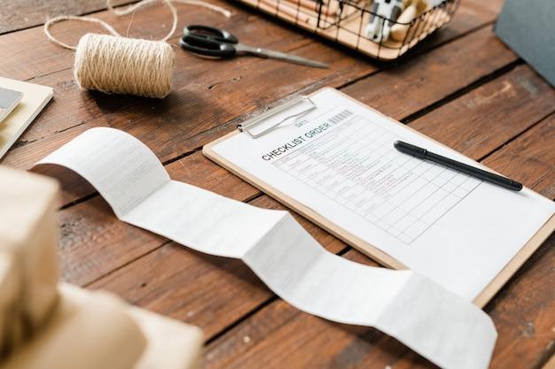 Presse-papiers avec liste de contrôle et stylo, bobine de fils, ciseaux et facture de réception sur table en bois