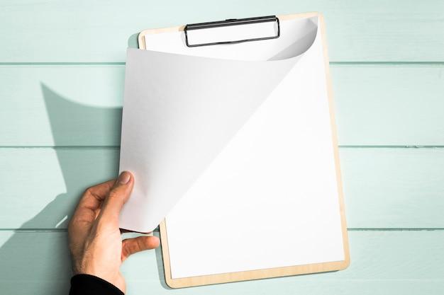 Presse-papiers et main tournant la vue de dessus de la page