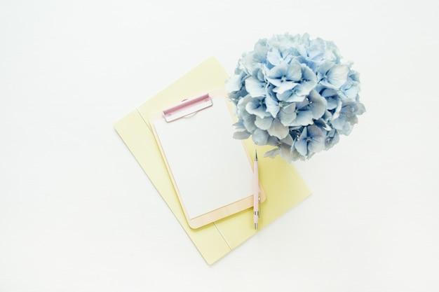 Presse-papiers maquette et bouquet de fleurs d'hortensia sur une surface blanche