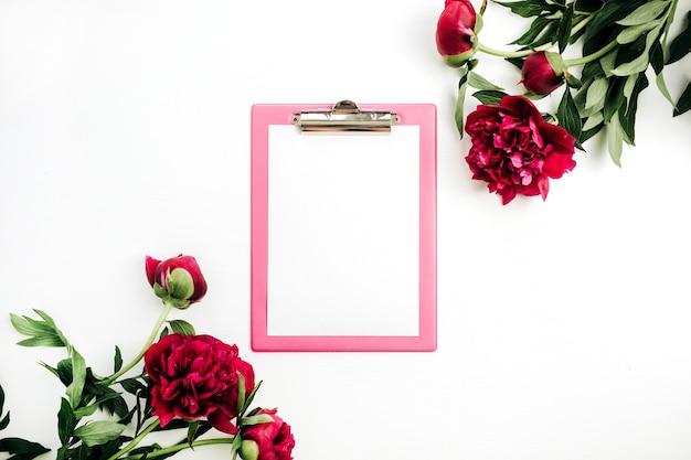 Presse-papiers maquette dans le cadre de fleurs de pivoine rose sur une surface blanche
