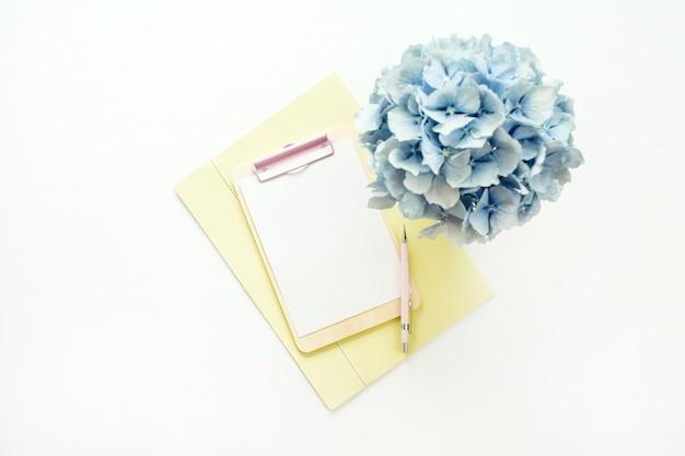 Presse-papiers maquette avec du papier blanc et bleu bouquet de fleurs d'hortensia sur une surface blanche