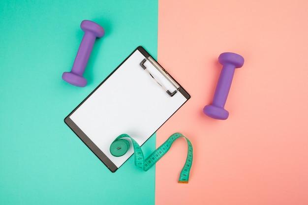 Presse-papiers de maquette avec haltère de gymnastique sur bleu et rose