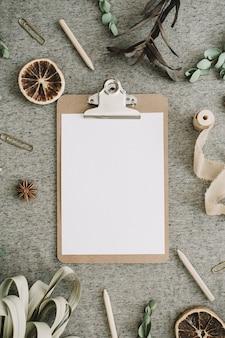 Presse-papiers avec maquette de papier vierge dans un cadre de branches d'eucalyptus, d'oranges et de feuilles séchées, ruban sur fond beige de couverture. mise à plat