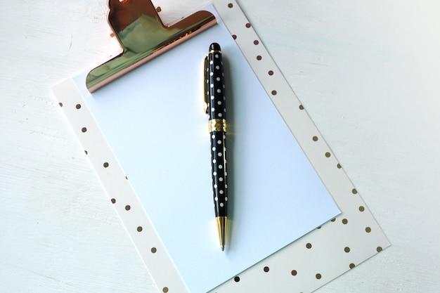 Presse-papiers maquette et stylo à pois blancs noirs sur le tableau blanc.