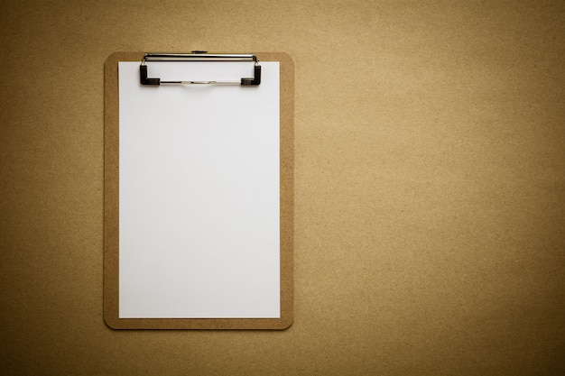 Presse-papiers marron et feuille de papier blanc sur fond de papier recyclé marron.