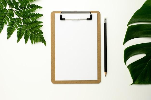 Presse-papiers et papier blanc sur fond de bureau blanc. conception à plat