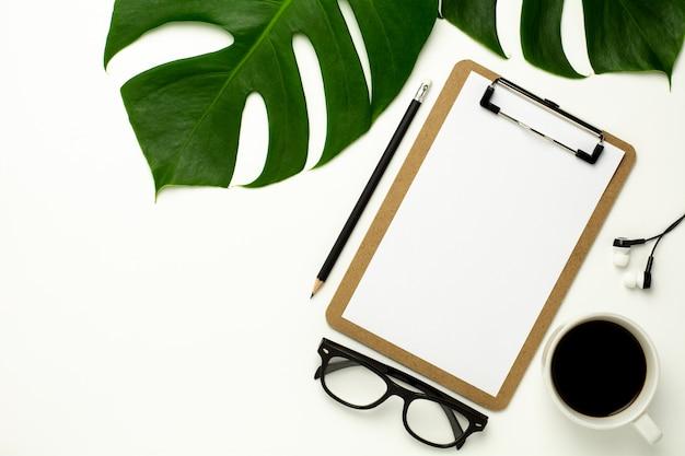 Presse-papiers et papier blanc sur fond de bureau blanc