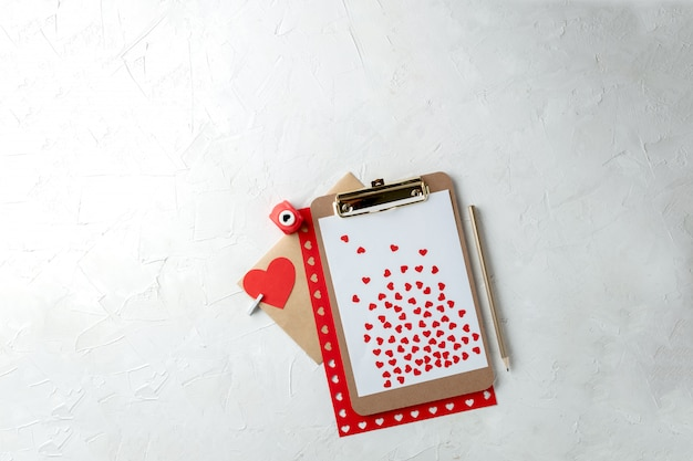 Presse-papiers avec papier vierge, coeurs de papier rouge