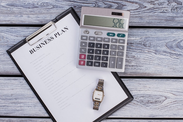 Presse-papiers avec plan d'affaires avec calculatrice et horloge de montre. vue de dessus à plat. table en bois blanc.