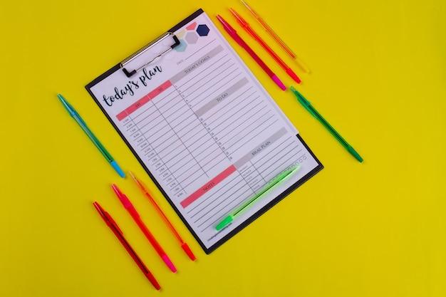 Presse-papiers avec plan d'aujourd'hui et stylos sur fond jaune.