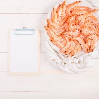 Presse-papiers avec plat de crevettes sur la table de la cuisine