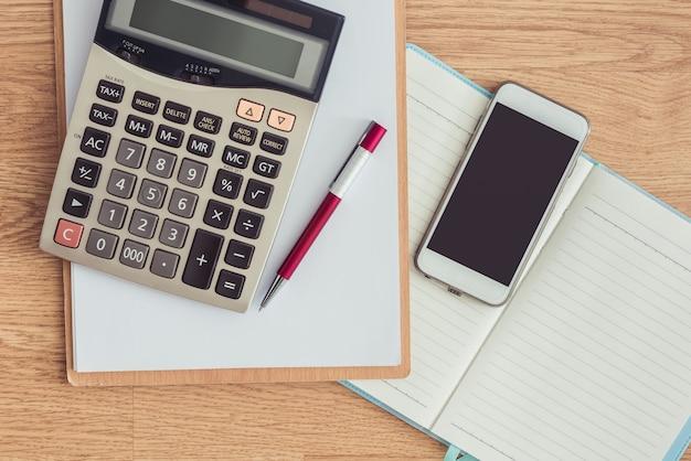 Presse-papiers avec un stylo et un cahier, calculatrice sur la table de bureau
