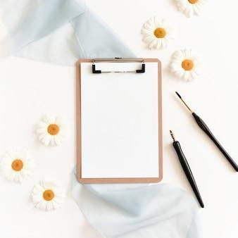 Presse-papiers, stylo calligraphique, pinceau, fleurs de camomille sur fond blanc