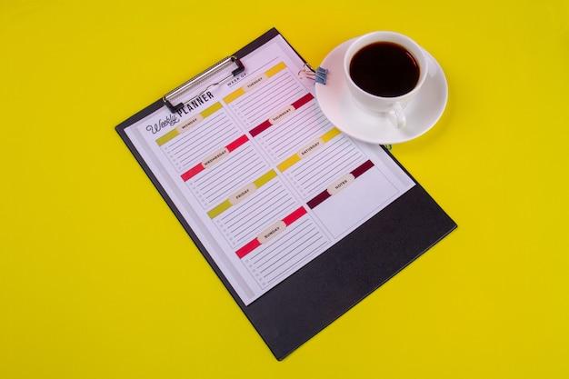 Presse-papiers avec une tasse de café fort dans une tasse blanche. isolé sur fond jaune.