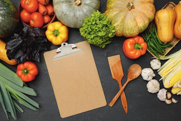Presse-papiers et ustensiles de cuisine entourés de légumes frais sur fond noir