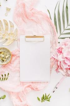 Presse-papiers vierge, fleurs d'hortensia rose et accessoires sur surface blanche